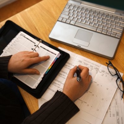 How to Create a Content Plan for Your Workshop – Whole Family Coaching. Woman sitting at desk writing in planner.