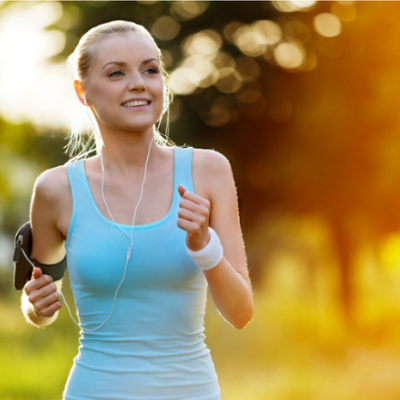 How to Create an Online Wellness Challenge – Whole Family Coaching. Woman running outdoors wearing an activity tracker.