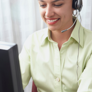 Work as a Home-Based Health Coach -Whole Family Coaching. Woman wearing a headset speaking with a client over the internet while working from a home office.