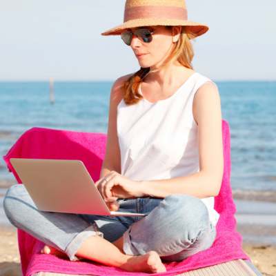 How to Plan a Workshop This Summer - Whole Family Coaching. Woman typing on laptop on the beach.